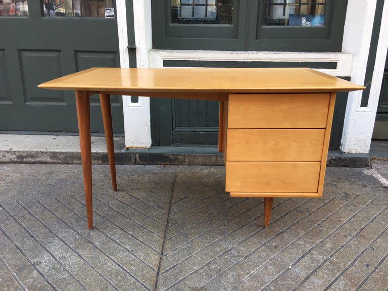 Florence Knoll style birch desk with walnut legs. Three pull out drawers on right side. Desk was refinished maybe 10 years ago and still presents very well. Nice ample work surface!
