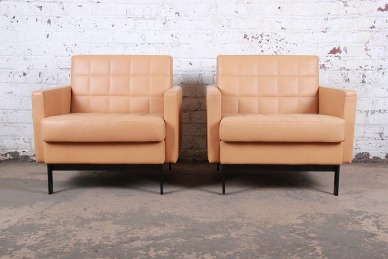 A gorgeous pair of modern leather lounge or club chairs  In the manner of Florence Knoll  Produced by Coalesse (a division of Steelcase)  USA, circa 1990s  Brown leather and black metal legs  Measures: 32.5