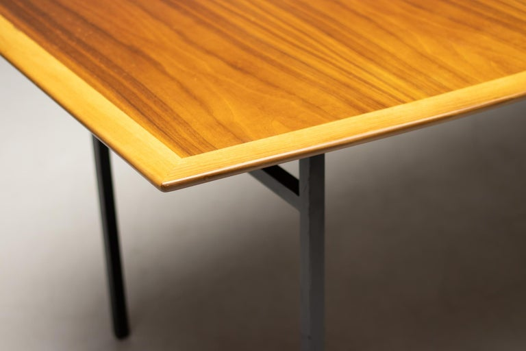 Florence Knoll model 578 dining table. Conference table with boat shaped top in walnut with an enameled square tubular steel base. The beautiful book matched walnut table top features a beveled edge. Marked with label, made by NK, Nordiska