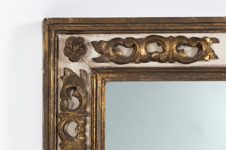 Florentine style gilded mirror, mid-20th century. Carved and gilded floral design on off-white painted panels within double moldings. Large, rectangular size frame with lovely burnished patina.