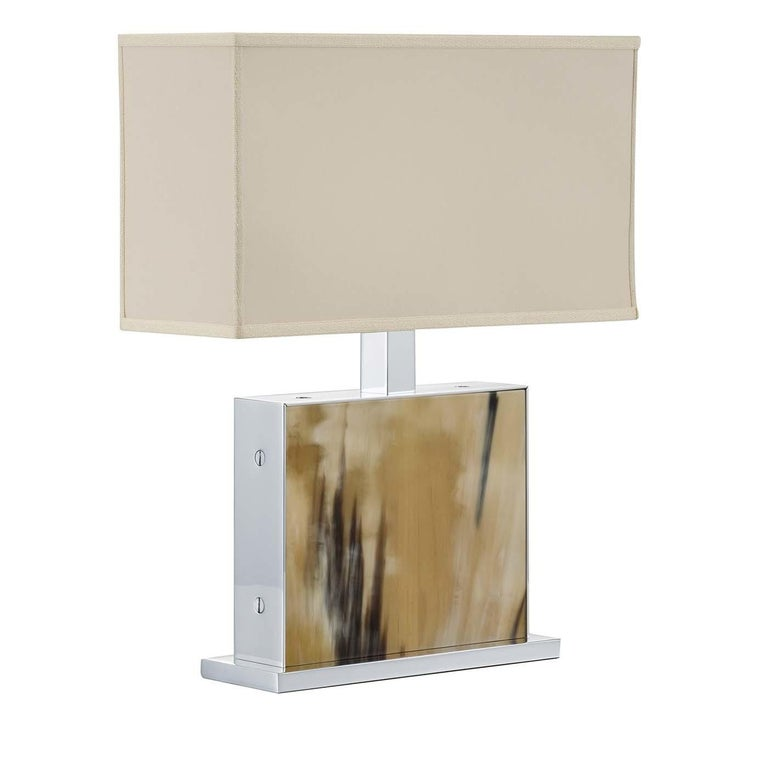 A superb piece of functional decor, this table lamp will enrich the look of a study, entryway, living room or bedroom with the opulence of its Horn inserts and the sleek lines of its stainless steel structure. The standout element is a rectangular