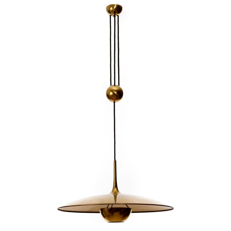 One of three height adjustable pendant lamps by Florian Schulz, Germany, manufactured in midcentury, circa 1970 (late 1960s-early 1970s). The fixture is made of solid brass with a polished and aged surface in a rich and warm tone with patina and