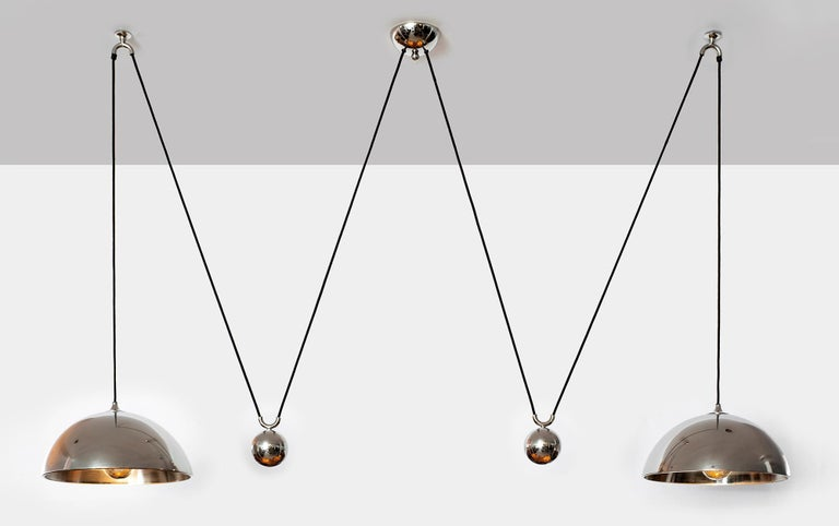 Double counterbalance pendant by Florian Schulz. Two nickel pendants suspended, each with their own nickel ball counter balance pulley system. One centre canopy supports both pendants. Each light is adjustable in height without effecting the other.