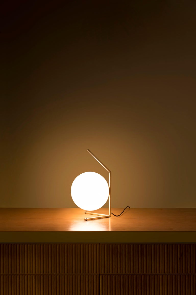 FLOS IC Lights T1 Low Table Lamp in Brass by Michael Anastassiades  Like the other pieces in his IC Light Series, the IC Lights T balances designer Michael Anastassiades' love of industrial simplicity with intricate symbolism. It provides diffused