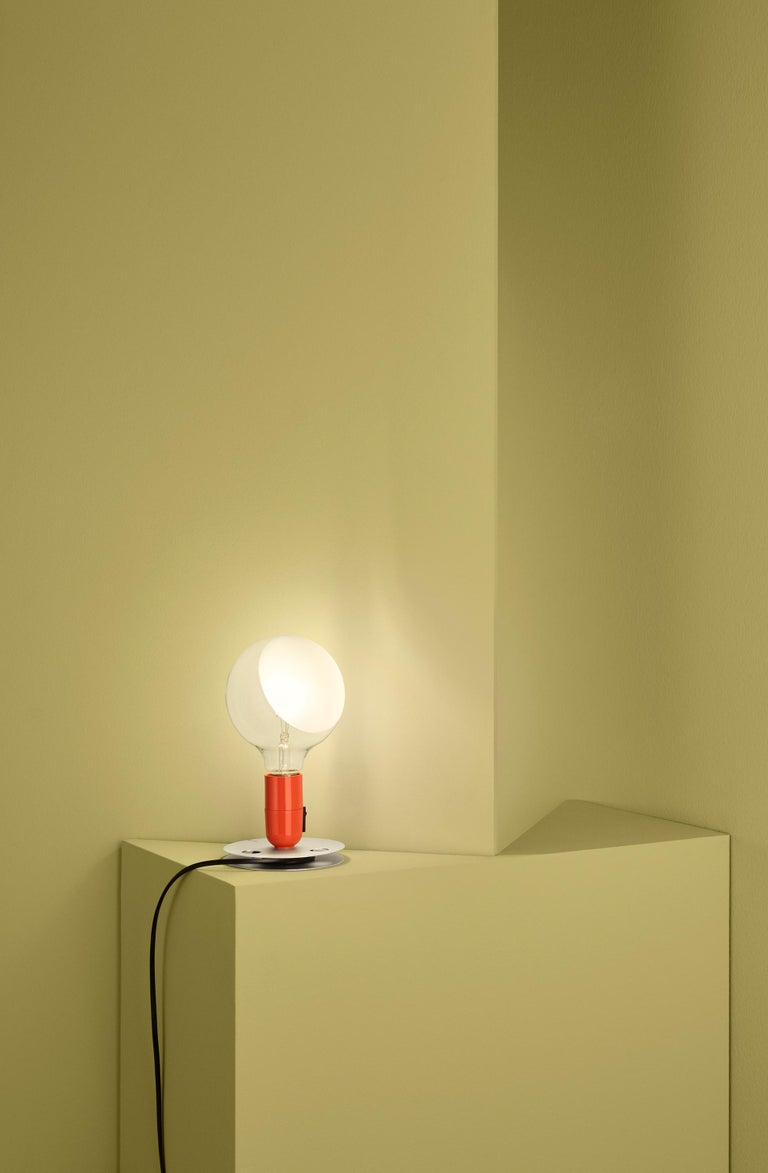 """Its name means, literally, """"bulb,"""" and it's easy to see why with one look at this playful Achille Castiglioni design. This unique table lamp provides direct and diffused light through a partly sandblasted clear globe. Its base is anodized aluminum"""