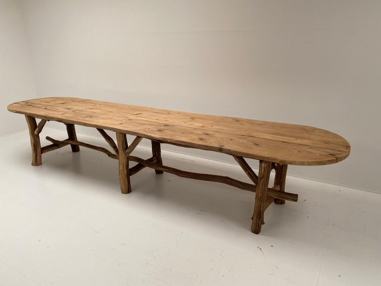 Beautiful table in pine wood from France with an elegant constructed base made of wood and grape branches, nice rounded form of the table top.