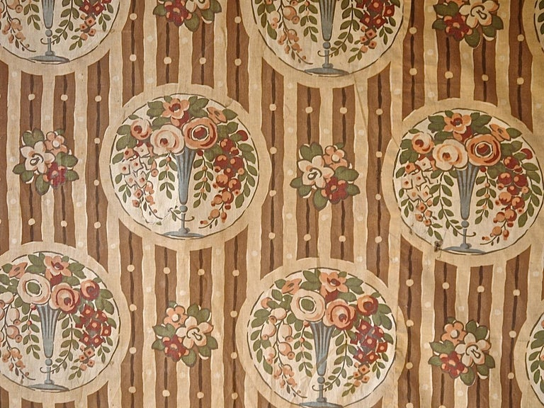 French circa 1920s block printed on a smooth cotton textile with a charming design of roses, trailing flowers and greenery spilling from a pale blue vase. It has been caught by the sun so now looks as though it has had a dip in a tea stained color.