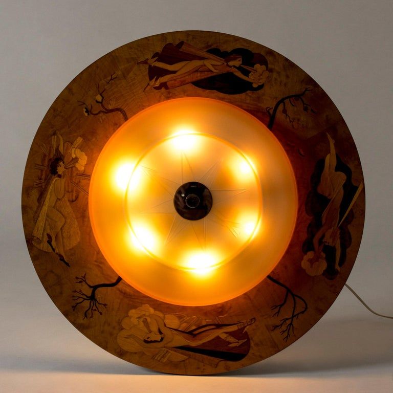 Striking, large 1930s flush mount ceiling light by Birger Ekman. Rare design with a round glass yellow nuance shade with the decor of a compass. Wide wooden frame with beautiful inlays of trees during different seasons and female wind spirits