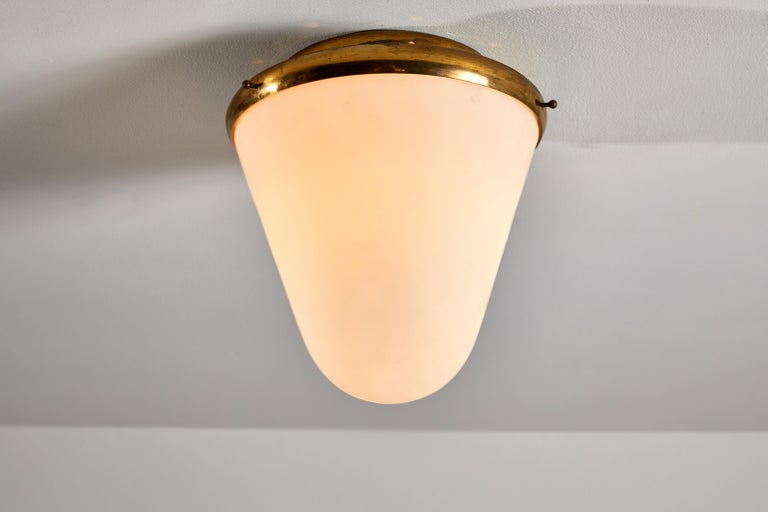 Flush mount ceiling light by Stilnovo. Manufactured in Italy, circa 1950s. Brushed satin glass diffuser, brass base and hardware. Rewired for US junction boxes.  Takes one E27 Edison bulb, 40 watts maximum. Bulb provided as a one time courtesy.