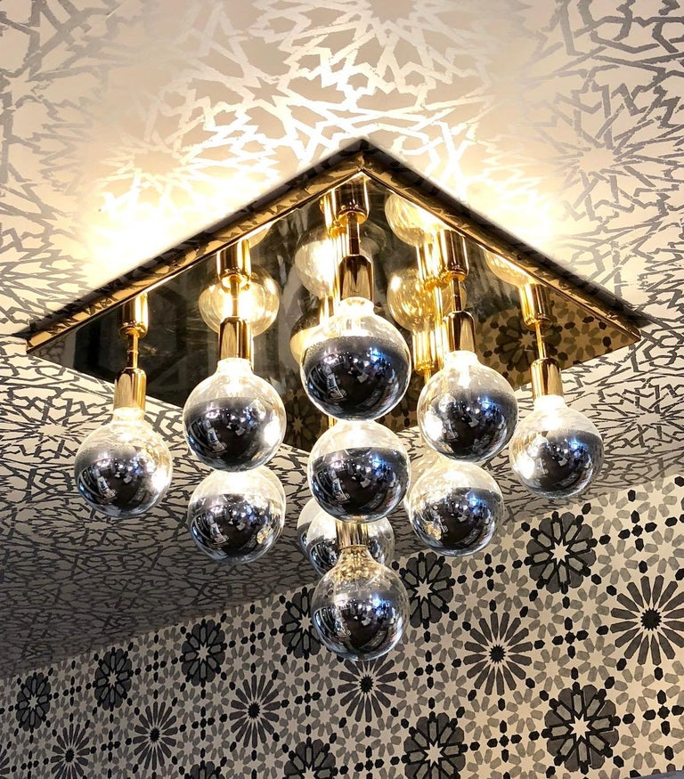 Brass flush mount light fixture. Square brass base with 13 dimmable mirrored top Bulbrites. Can be installed as a ceiling or wall/sconce light.