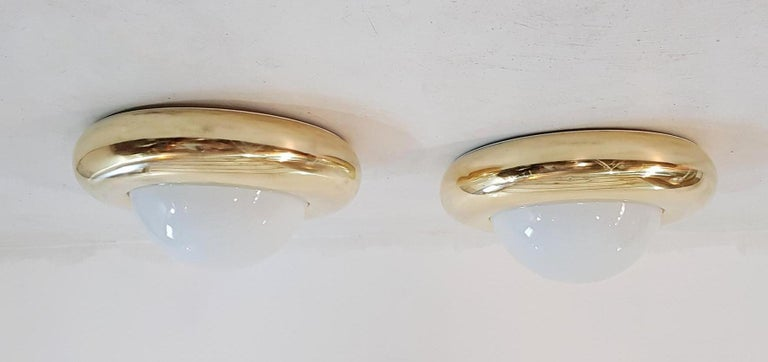A large pair of lamps that can be used as flush mounts or wall sconces in brass and opaline glass. Each light takes one E27 bulb. The brass has been professionally rebuffed.