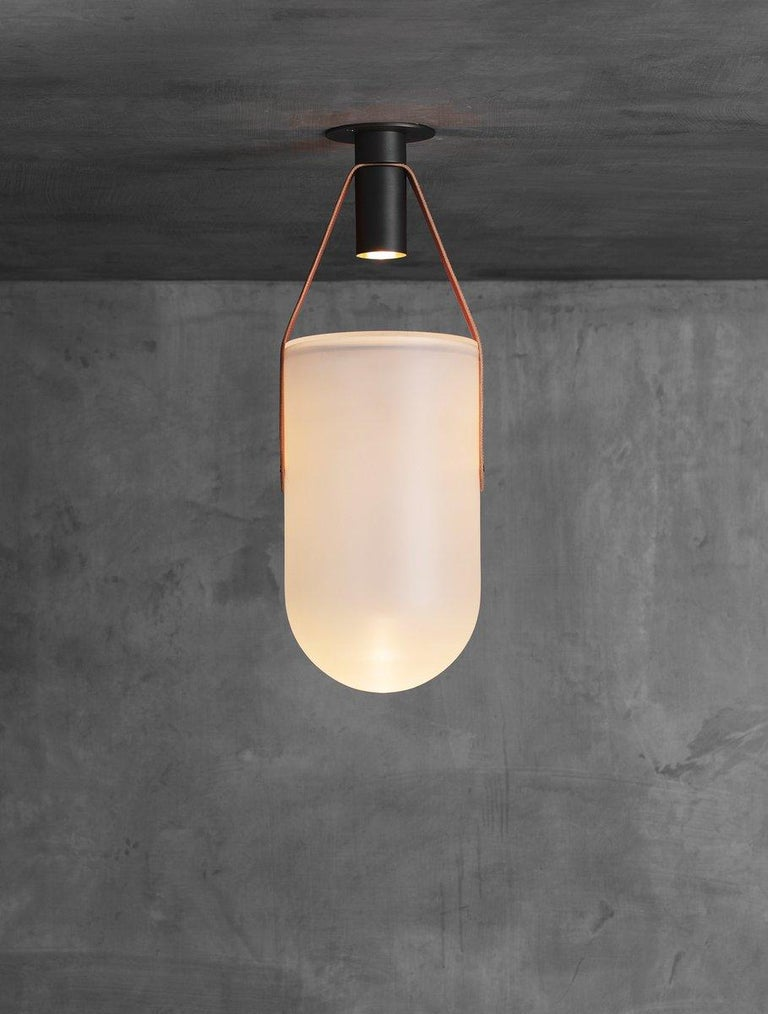 A spot bulb shoots light into a sandblasted glass dome that is suspended by a leather strap and brass hardware. The fixture creates a warm glow inside the glass as well as casting dramatic shadows onto the ceiling. UL certified.