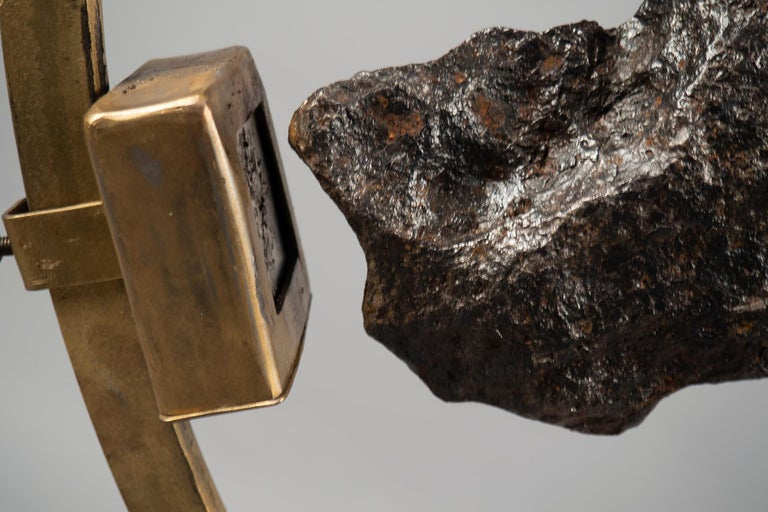 Tall 3/4 circle brass structure holding a meteorite fragment (5kg) from Campo del Cielo, Argentina. The meteorite is held in place by a strong rare earth magnet mounted on the structure. The base is a weighted brass or walnut box.