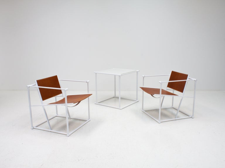 A pair of steel and leather FM62 chairs and table by Radboud Van Beekum for Pastoe, 1980s.  Constructed from geometrically folded steel with leather seating. Inspired by the designs of Gerrit Rietveld and following the traditions of the De Stijl