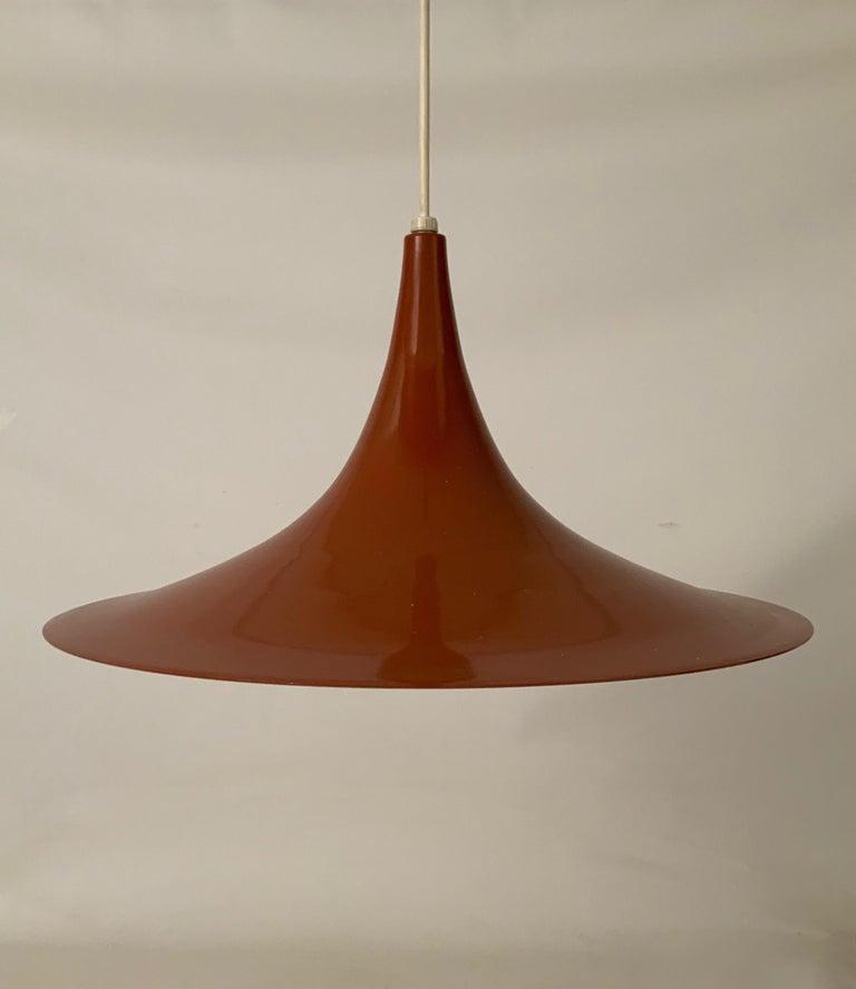 Burnt orange exterior enamel with white interior pendant light designed for Fog & Mørup by Torsten Thorup and Claus Bonderup, circa 1967. Classic iconic Danish modern design. Excellent condition.  Measures: 19.25