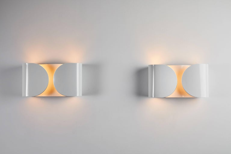 Foglio sconce by Tobia Scarpa. Current production by Flos. Foglio wall lamp provides indirect light. The lamp's body is formed by power-painted pressed steel. The two lamp supports are injection-molded white nylon. It is HPF electronic ballast