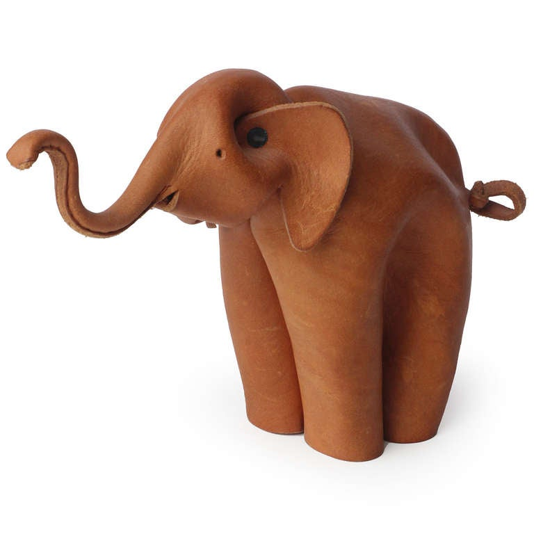 An elephant with an upturned trunk formed from a single sheet of crimped, pinched, cut and riveted leather.
