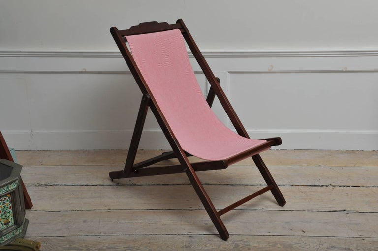 A folding and adjustable (three settings) teak lounge chair from the 1940s with a red and white striped sling seat. The canvas has been replaced and we include a matching, detachable pillow. 1940s, British Campaign. There is a very easy mechanism