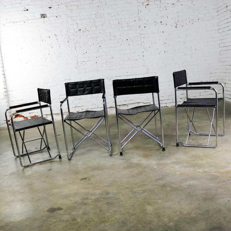Handsome set of four folding Campaign style director's chairs comprised of black vinyl sling seats and back, and chrome metal frame with plastic arm rests. These are done in the style of Gae Aulenti's April 2120 chair by Zanotta. This set of four