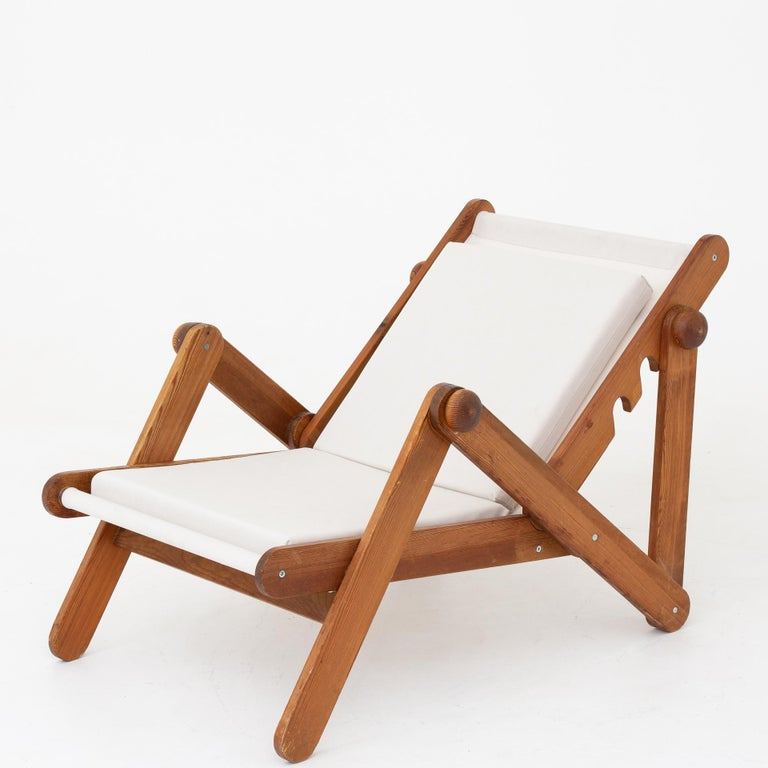 Folding chair in patinated pine with adjustable backrest. Upholstered with new canvas. Maker Brio Sweden.
