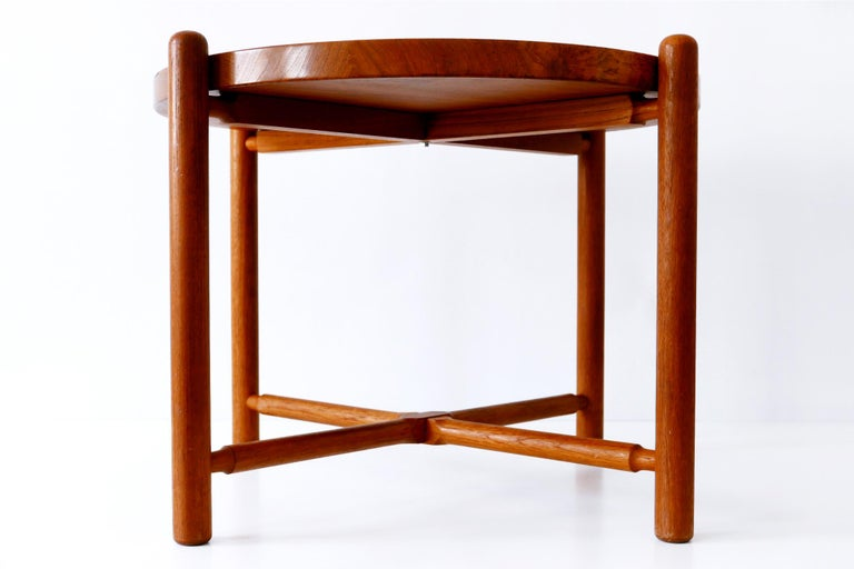 Rare Mid-Century Modern folding coffee table with massiv teak tray and base. The table top with a delicate lip sits loose on the base which is foldable.   At first sight it seems to be similar to the folding table AT-35 of Hans J. Wegner. But