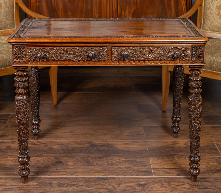 An Anglo-Indian oak table from the early 20th century, with two drawers and richly carved foliage decor. Born at the turn of the century, this exquisite oak table features a rectangular top with rounded corners and delicately carved frame, sitting