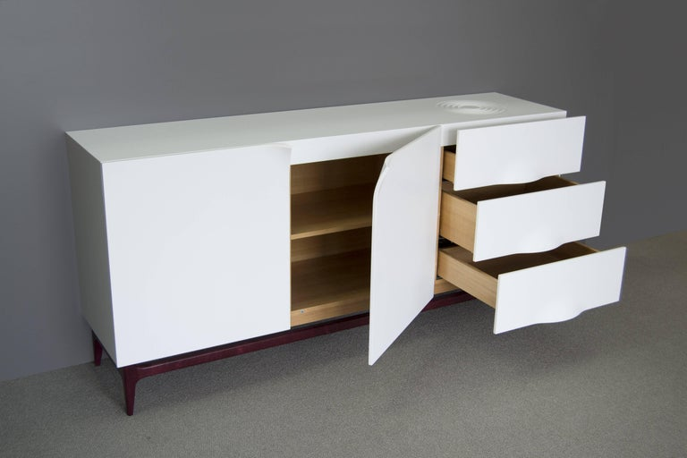Storage cabinet with contemporary design. Opening with two doors and three drawers. Solid Corian exterior - Color: White glacier. Interior comprises two shelves all in Aniégré wood veneer - Color: Natural wood. Base in solid amaranth.  A