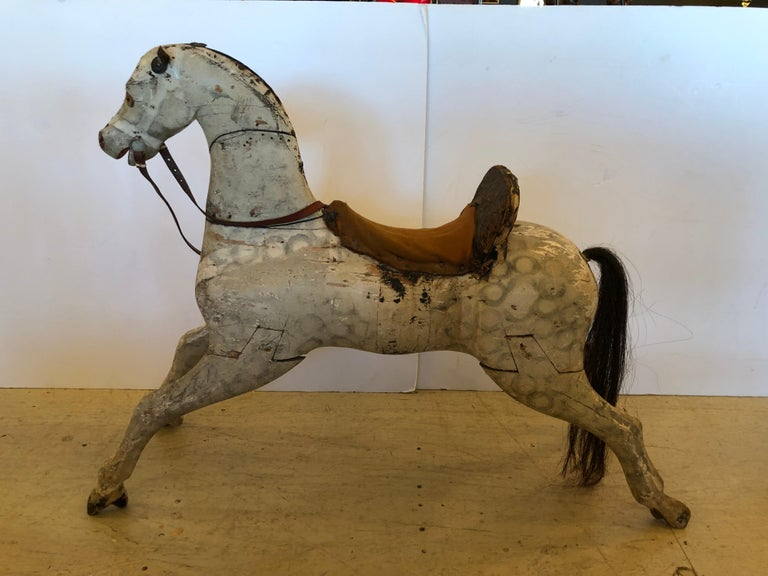 19th century wooden rocking horse with rocking base removed. Made of wood, horse has a worn leather saddle and leather reins. Eyes are made of glass and horse hair tail. A wonderful piece of Americana.