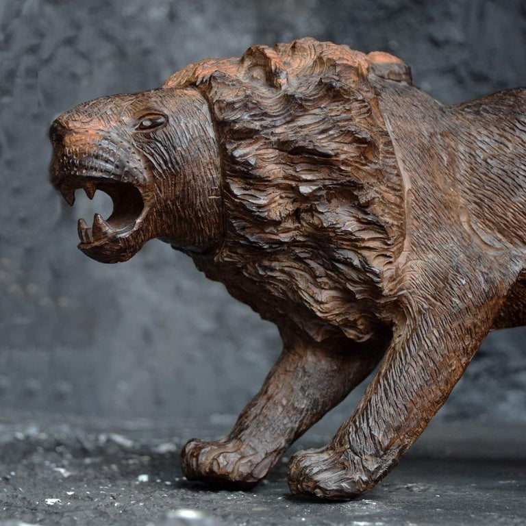 An unusually detailed example of a mid-20th century Folk Art lion figure. Unique in its formed with one rear leg raised as if it has a thorn in its foot. The etching across the surface of this statue is well crafted and detailed, a very tactile,