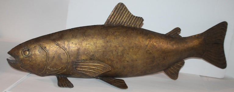 This amazing 20th century handmade Folk Art gilded metal sculpture of a fish is in fine condition. It is unsigned and not sure if it was made to hang in a fish house or grill. Perhaps on a fresh fish market. Great as display on a shelf or cupboard.