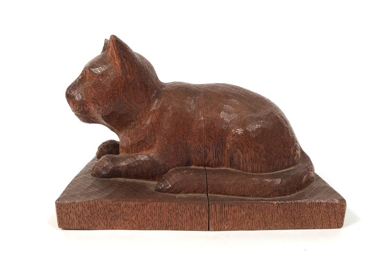 A beautifully hand carved wood folk art sculpture of a cat, in oak, resting, with alert expression, on a rectangular plinth, American, circa 1890-1900.