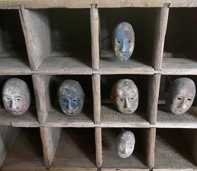 Folk Art mask shadowbox: A very curious and unique vintage Folk Art shadowbox comprising six miniature hand-sculpted earthenware masks mounted in an antique wooden Coca Cola crate. Each hand molded clay face differs to a greater or lesser extent