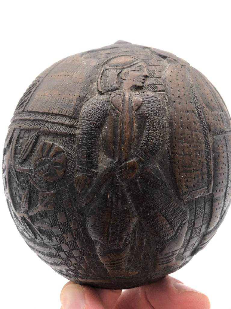 Sailors from various countries would carve green coconuts to help pass the time. This particular example is early and dates to circa 1800. It has some of the most interesting and folky figures, when compared with other examples. There are 3 full