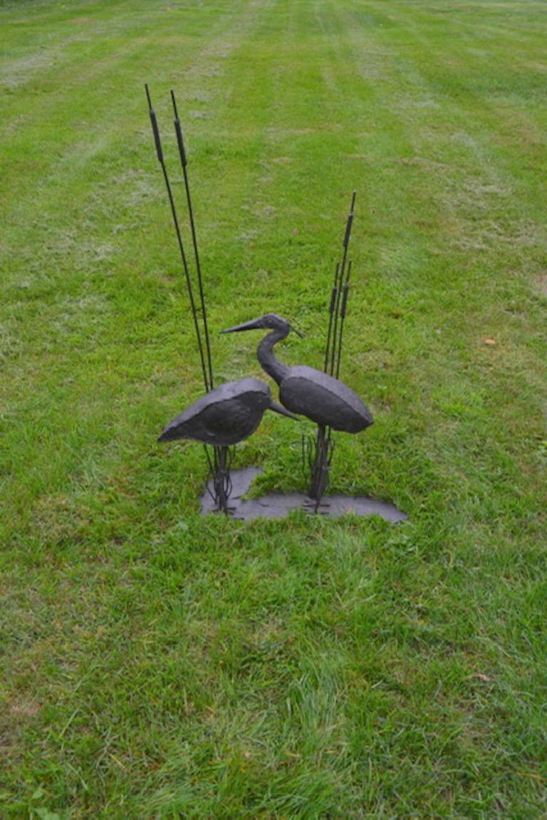 A wrought iron sculptural group of two shorebirds, a sandpiper and heron, standing among cattails, with soldering worked to indicate the heron's feathers, American, circa 1960. Measures: 46 ins. high, 29 ins. wide, 13 ins. deep.