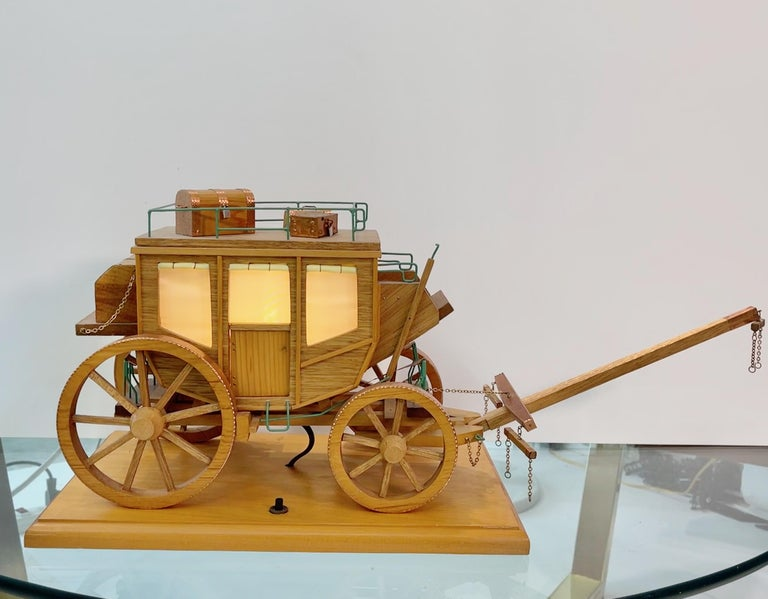 Remarkably well preserved 1950's Folk Art model of a stage coach illuminated from within, complete with working carriage springs and movable yoke and luggage. On/off switch on wooden base. Great nightlight.. Constructed from thin plywood with hand