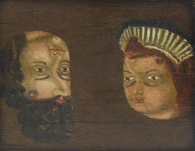 Folk Art trompe l'oeil reversible double portrait, oil on board depicting a man on the left and a woman on the right; when reversed a different man and woman appear; the wormy panel attached to the frame with wrought iron nails. (See
