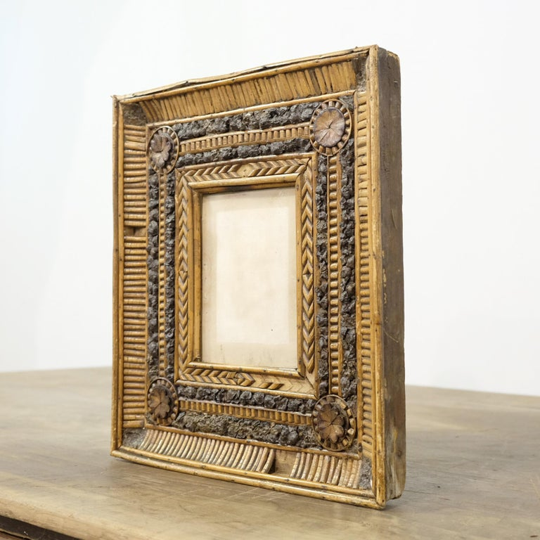 A delightfully charming and unusual 19th century Folk Art picture frame. With an extensive amount of applied intricate twig and bark decoration around a small glazed aperture. With some losses which we feel adds to its character. A great piece for a