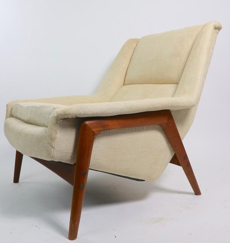 Classic Folke Ohlsson lounge chair manufactured by DUX of Sweden. This example is structurally sound and sturdy, the fabric is worn and will need to be replaced. Measures: Total H 34 x arm H 18 x seat H 16 inches.