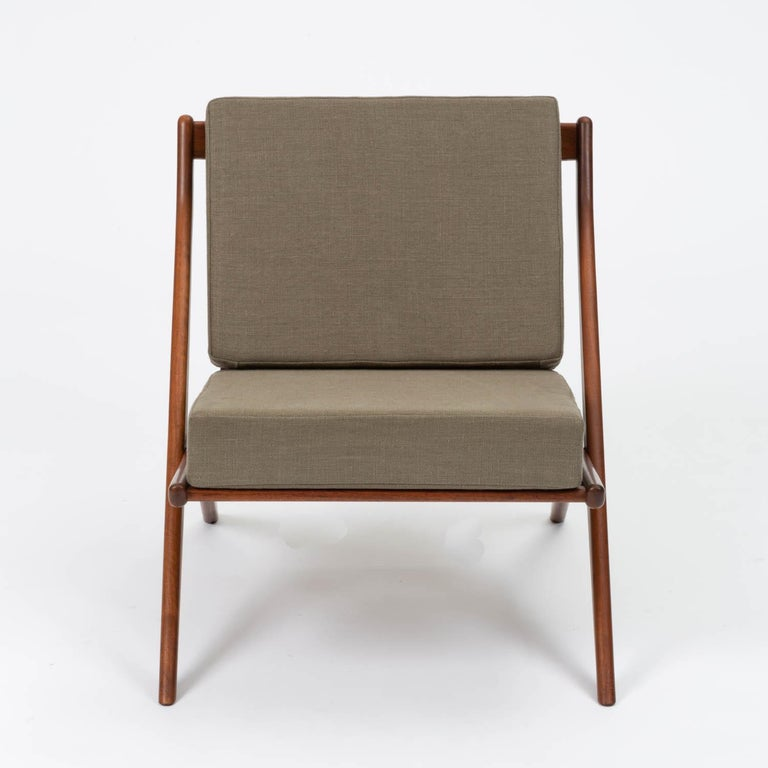 Scissor lounge chair by Folke Ohlsson for DUX, Sweden, circa 1950s. The chair features a scissor-like teak frame with slatted wood backrest and newly upholstered cushions in gray Belgian linen.  Condition: Excellent restored condition with new