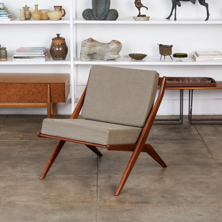 Scissor lounge chair by Folke Ohlsson for DUX, Sweden, circa 1950s. The chair features a scissor-like teak frame with slatted wood backrest and newly upholstered cushions in gray Belgian linen.  Condition: Excellent restored condition with new foam