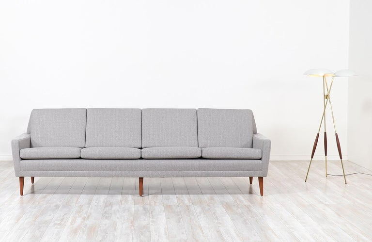 Elegant modern four-seat sofa designed by Folke Ohlsson for DUX in Sweden, circa 1950s. This stylish model 66-S4 sofa features a sturdy teak wood construction with new high-density foam, webbing straps, and tweed upholstery on the cushions for the