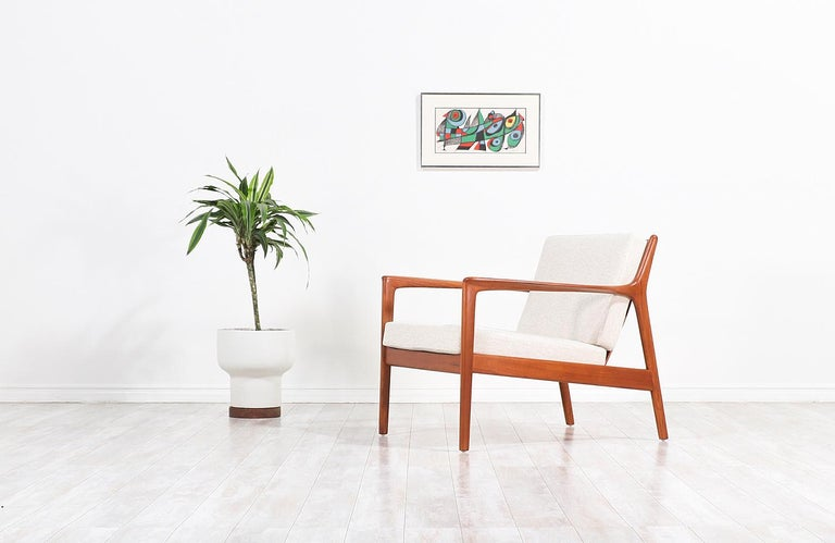 Stylish model 75-C modern lounge chair designed by Folke Ohlsson for DUX of Sweden, circa 1950s. This chair features a solid teak wood frame with loose cushions and eight slats on the open back, creating soft curves for a clean aesthetic. The wood