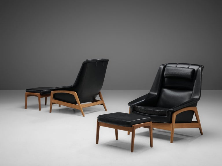Folke Ohlsson for DUX, pair of lounge chairs, model 'Profil' with ottoman, black leather, oak, Sweden, 1960s  Pair of lounge chairs with ottomans, designed by Folke Ohlsson for DUX. On a bright oakwooden frame sits the bulky seating in black