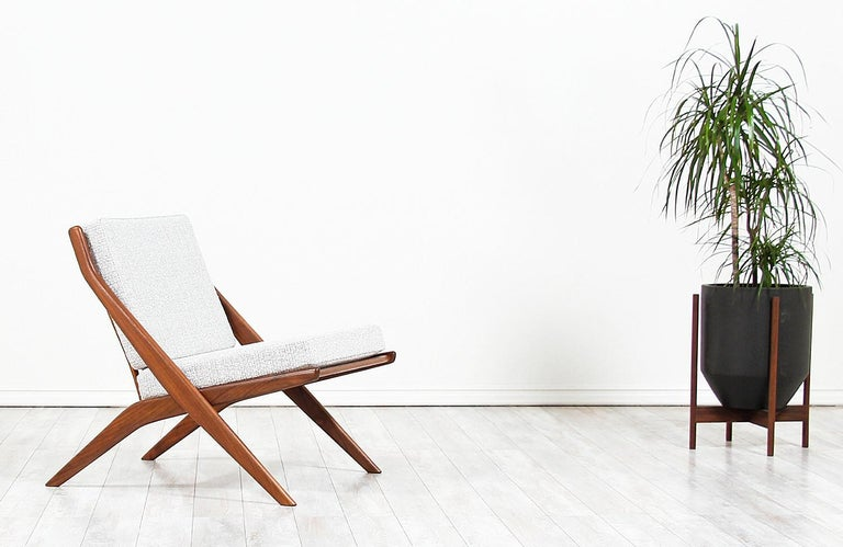 Elegant modern lounge chair designed in Sweden by Folke Ohlsson for DUX of Sweden, circa 1950s. This Minimalist lounge chair features a solid walnut wood frame with new high-density foam cushions and light-colored tweed fabric upholstery. This