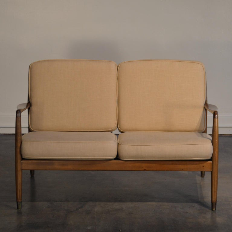 Designed for DUX by Folke Ohlsson and produced in the 1960s. This is a charming and lightweight Scandinavian Modern loveseat/settee made from stained and beech wood.  Retains DUX paper label. The settee has new straps for the seat base, new