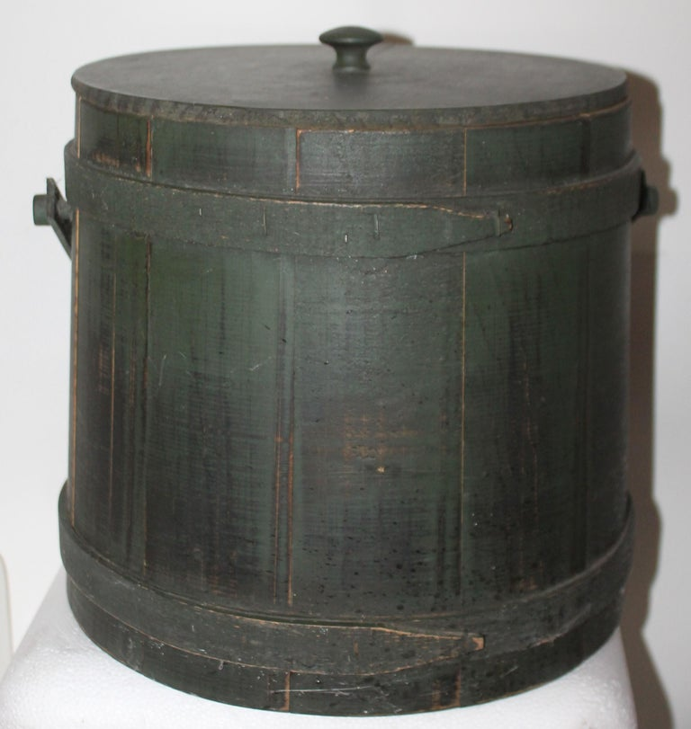 This folky original green painted furkin or sugar bucket has the original lid. It is in very good condition.