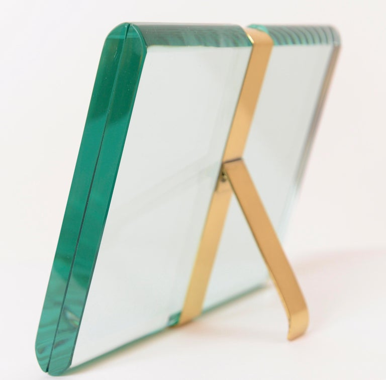 An exquisite St Gobain crystal picture frame designed and produced by the Milanese company, Fontana Arte, in 1955. The slender brass fitting and back support couples the two pieces of beveled glass enabling the user to place a photograph between