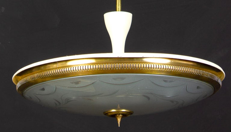 Rare and early pendant by Luigi Brusotti with a precious engravings on the crystal etched acid disc, supported by a partial ivory lacquered brass frame.