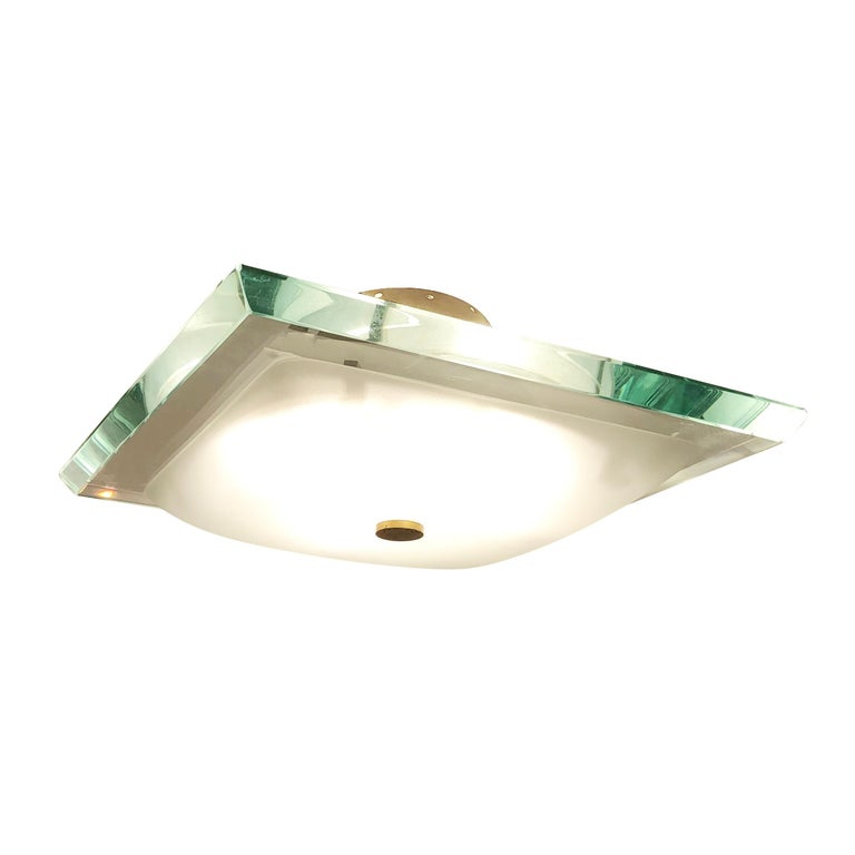 Fontana Arte flushmount designed by Max Ingrand in the 1960s featuring a thick square glass. As typical of glass of the era it has a green edge which creates a beautiful emerald color when lit or seen from certain angles. The four candelabra sockets