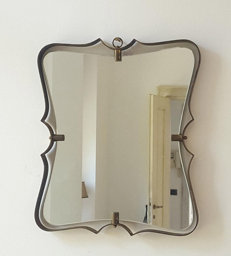 Elegant mirror with curved patinated brass frame and bevelled original mirror inside. The four brass hooks support the mirror thanks to the recess of the brass cylinders.  Bibl.: Vitrum, n.10 August 1950 for similar example  The mirror inside is